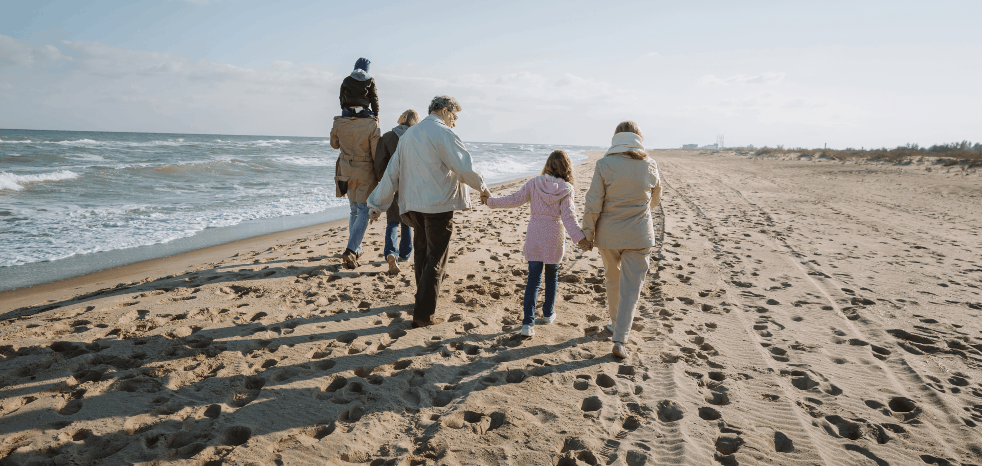 Multi-generational family walking on beach.